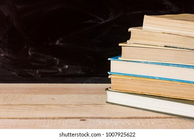 Stack of books on a wooden desk with a blackboard in the background