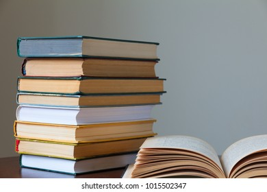a stack of books on a wooden old table and a light background