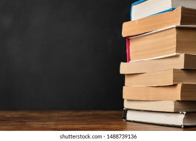 Stack of books on wooden school desk against the background of the blackboard