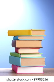 Stack of books on wooden table on blue background