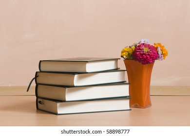 stack of books and an orange vase with colored flowers