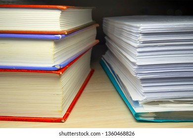 A stack of books and papers on the desktop, symbolizing learning, laws and regulations, a huge amount of information