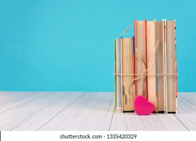 Stack of books and pink heart. Books with jute ribbon bow as gift on blue background. Education background with copy space, back to school concept.