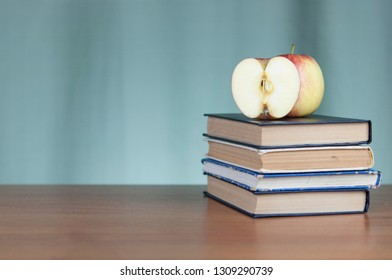 Stack of books and red apple on wooden table