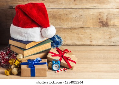 A stack of books, Santa Claus's cap, an alarm clock, gift boxes on a wooden background. Concept of New Year and Merry Christmas.