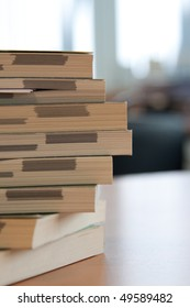 Stack of books standing on a wooden table