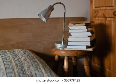 Stack of books and table lamp near bed