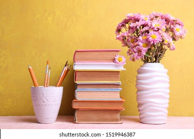 Stack of books and vase with bouquet of chrysanthemums on yellow background. Concept teacher's day.