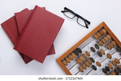 Stack of books with vintage abacus and glasses on white background. Economic calculation. Top view
