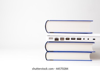 stack of books and white laptop computer