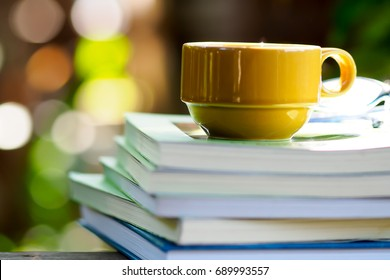 Stack of books and yellow cup of coffee on a green natural background. Coffee in the garden with a book.  Stack of books.
