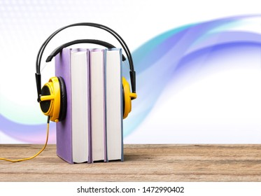 Stack of books with yellow headphones on a wooden table