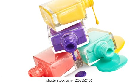 Stack of bottles with spilled nail polish isolated on white background