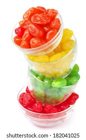 Stack of bowls with colorful candied fruits isolated on white background.