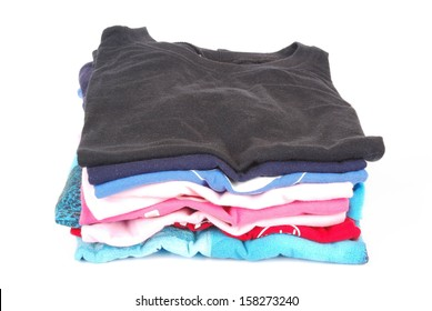 A stack of a boys ironed t-shirts in various colors. Image isolated on white studio background.