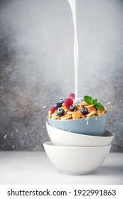 A stack of breakfast bowls, topmost bowl filled with freshly made pancake cereal and fresh berries. Milk is poured on the top of the cereal, drops of milk scatter all around