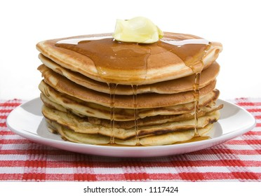 Stack of Breakfast Pancakes – A big stack of pancakes, drizzled with syrup and a dollop of butter. Country style with red checkered place mat.