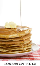 Stack of Breakfast Pancakes and Syrup – A stack of pancakes, with syrup drizzling down over the top. A dollop of butter sits on top. Country style with red checkered place mat.