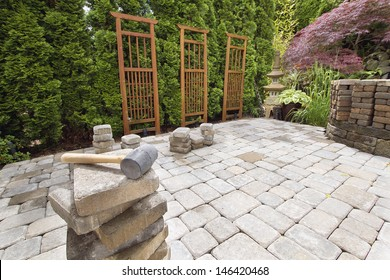 Stack of Brick Pavers for Hardscape in Backyard Landscaping with Trellis and Trees