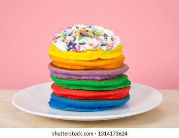 Stack of bright colorful pancakes topped with whipped cream and candy sprinkles with Pink background. Fairy pancakes for National International Pancake day.