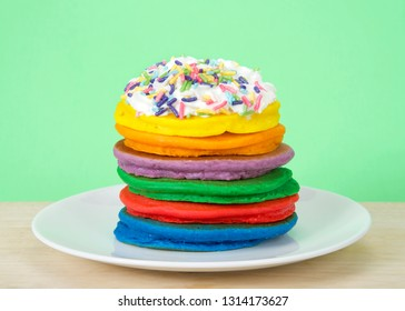 Stack of bright colorful pancakes topped with whipped cream and candy sprinkles with green background. Fairy pancakes for National International Pancake day.