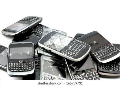 stack of broken mobile phones