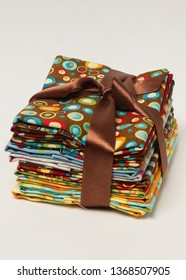 stack of brown patterns fabric with gift bow from above