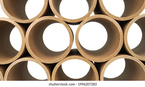 Stack of a bunch of paper tube cores, tissues, in front of white wall . Raw product material of brown paper rolls.