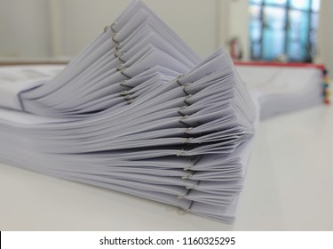 Stack of business report on desk with blurred of office room interior background.
