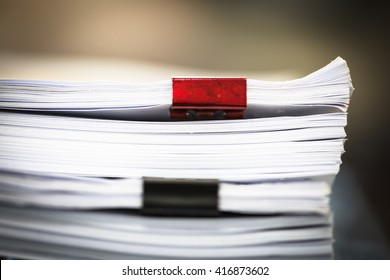 Stack of business report paper files with red and black clips