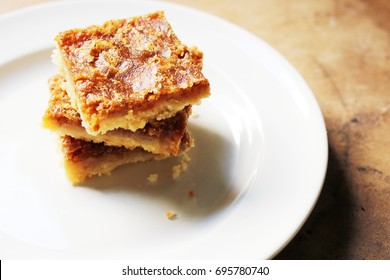 Stack of Butter Tart Squares on A White Plate