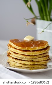 A stack of buttered pancakes on a white porcelain plate. Blurred background with spring flowers