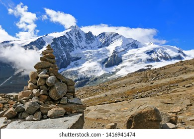A stack of cairn at Gamsgrube Nature hiking trail along the Pasterze Glacier with the view of Grossglockner mountain range in the background, Austria