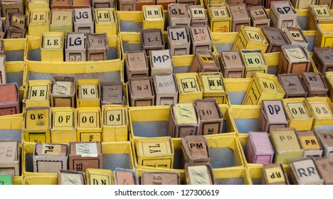Stack of cardboard boxes with alphabet letters  and syllables. Vintage game at flea market in Paris (France).