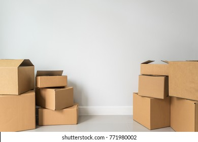 Stack of cardboard boxes in empty room in new home with copy space