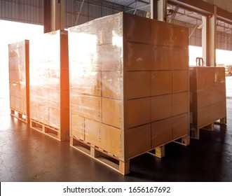 Stack of cardboard boxes wrapping plastic on pallets, package boxes, loading freight truck , warehouse industrial service logistics, shipment goods transport