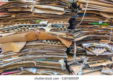 Stack of cartons and paper waiting to be picked up by the garbage trucks. Concept of recycling of waste paper or wastepaper.