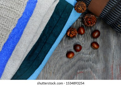 A stack of cashmere and wool sweaters,a woven brown bag,fir cones and chestnut nuts create an autumnal warm atmosphere.