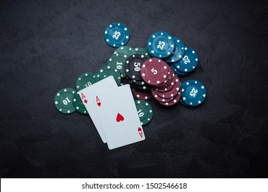 A stack of casino chips and two playing cards. Two aces on a black background