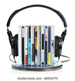 Stack of CDs with HI-Fi headphones on vintage reel of audio tape on white background