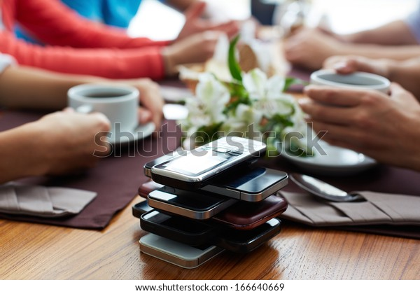 Stack of cellphones with group of friends on background