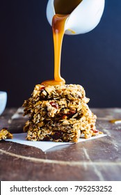 Stack of chewy almond and oat bars drizzled with caramel sauce from a white pitcher and topped with salt on brown surface with a navy background.