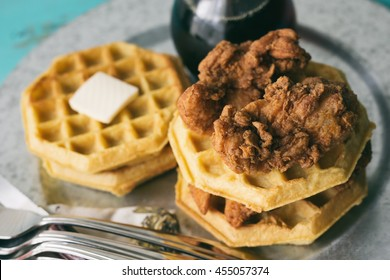 Stack of chicken and waffles on a galvanized steel plate. Maple syrup on the side.