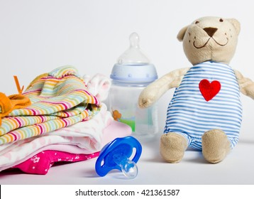 A stack of children's clothing, toys, pacifier on a white background. Preparing for motherhood. Shopping for baby.