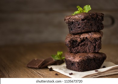 A stack of chocolate brownies on wooden background with mint leaf on top, homemade bakery and dessert