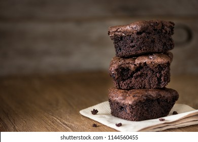 A stack of chocolate brownies on wooden background, homemade bakery and dessert