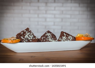 A stack of chocolate brownies served on a wooden table. Homemade dessert.