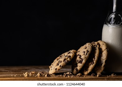 A stack of chocolate chip cookies leaning on a bottle of milk.