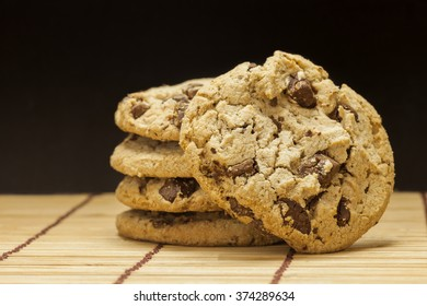 Stack of Chocolate chip cookies on wooden with black background.