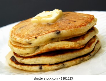 stack of chocolate chip pancakes with butter and syrup